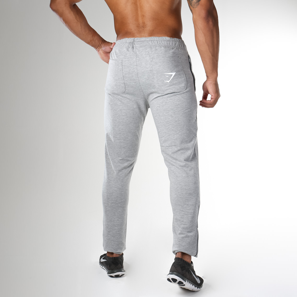 From behind: Gymshark Fit Tapered Bottoms in Grey